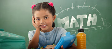 Composite image of smiling girl with lunch box at table Royalty Free Stock Photo