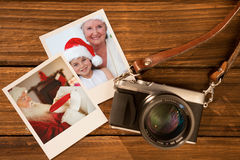 Composite image of smiling grandmother and little girl baking christmas cakes. Smiling grandmother and little girl baking Christmas cakes against instant photos Royalty Free Stock Image