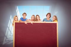 Composite image of smiling group of people with a blank space as they point to it Royalty Free Stock Photos
