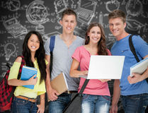 Composite image of a smiling group of students holding a laptop while looking at the camera Royalty Free Stock Photo