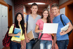 Composite image of a smiling group of students holding a laptop while looking at the camera Stock Photography