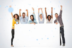 Composite image of smiling group of young friends showing large poster and cheering Royalty Free Stock Photography