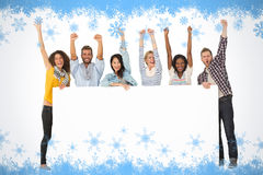 Composite image of smiling group of young friends showing large poster and cheering Stock Photos