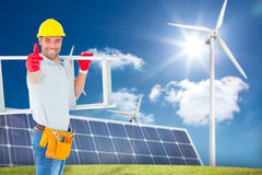 Composite image of smiling handyman carrying ladder while gesturing thumbs up. Smiling handyman carrying ladder while gesturing thumbs up against large solar Royalty Free Stock Images