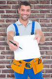 Composite image of smiling handyman giving clipboard for signature Royalty Free Stock Photo