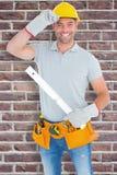 Composite image of smiling handyman holding spirit level Royalty Free Stock Image
