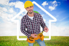 Composite image of smiling handyman holding tape measure Stock Image