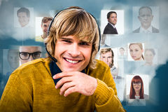 Composite image of smiling hipster businessman using headset. Smiling hipster businessman using headset against dark blue background Royalty Free Stock Image