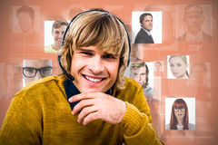 Composite image of smiling hipster businessman using headset. Smiling hipster businessman using headset against orange background Royalty Free Stock Photo