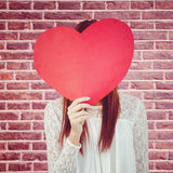 Composite image of smiling hipster woman behind a big red heart Stock Image