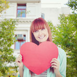 Composite image of smiling hipster woman behind a big red heart Royalty Free Stock Image
