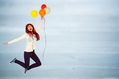 Composite image of smiling hipster woman holding balloons. Smiling hipster woman holding balloons against bleached wooden planks background Stock Photos