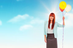 Composite image of smiling hipster woman holding balloons. Smiling hipster woman holding balloons against blue sky Royalty Free Stock Photo