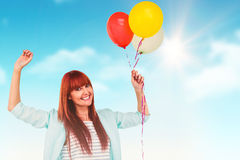 Composite image of smiling hipster woman holding balloons. Smiling hipster woman holding balloons against blue sky Stock Images