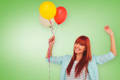 Composite image of smiling hipster woman holding balloons. Smiling hipster woman holding balloons against green vignette Stock Photography