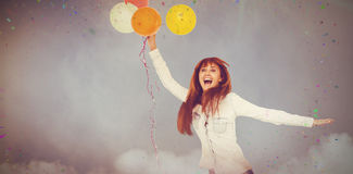 Composite image of smiling hipster woman holding balloons. Smiling hipster woman holding balloons against illuminated disco lights at disco Stock Image