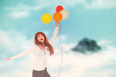 Composite image of smiling hipster woman holding balloons. Smiling hipster woman holding balloons against mountain peak through the clouds Stock Photo
