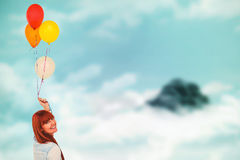 Composite image of smiling hipster woman holding balloons. Smiling hipster woman holding balloons against mountain peak through the clouds Royalty Free Stock Images