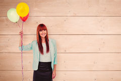 Composite image of smiling hipster woman holding balloons. Smiling hipster woman holding balloons against overhead of wooden planks Royalty Free Stock Image