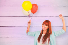 Composite image of smiling hipster woman holding balloons. Smiling hipster woman holding balloons against painted blue wooden planks Stock Image