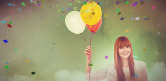 Composite image of smiling hipster woman holding balloons. Smiling hipster woman holding balloons against smoke at illuminated disco Royalty Free Stock Photo