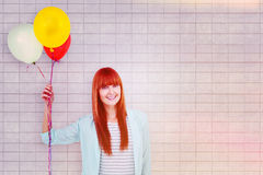 Composite image of smiling hipster woman holding balloons. Smiling hipster woman holding balloons against textured background Stock Images