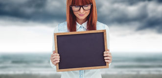 Composite image of smiling hipster woman holding blackboard Royalty Free Stock Photo