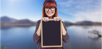 Composite image of smiling hipster woman holding blackboard Stock Photography