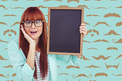 Composite image of smiling hipster woman holding blackboard Stock Photo