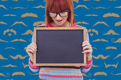 Composite image of smiling hipster woman holding blackboard. Smiling hipster woman holding blackboard against composite image of mustaches Stock Photos