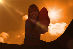 Composite image of smiling hipster woman holding a red heart. Smiling hipster woman holding a red heart against a cloudy sky royalty free stock photo