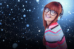 Composite image of smiling hipster woman listening music with headphones Stock Image