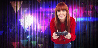 Composite image of smiling hipster woman playing video games. Smiling hipster woman playing video games against wooden planks background Royalty Free Stock Photos