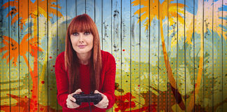 Composite image of smiling hipster woman playing video games. Smiling hipster woman playing video games against wooden planks background Stock Photo