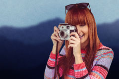 Composite image of smiling hipster woman taking pictures with a retro camera Royalty Free Stock Images