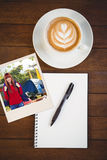 Composite image of smiling hipster woman with a travel bag taking selfie. Smiling hipster woman with a travel bag taking selfie against cup of cappuccino with Royalty Free Stock Photography