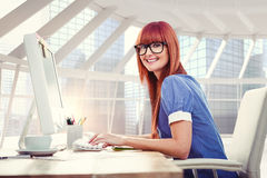 Composite image of smiling hipster woman typing on keyboard Stock Image