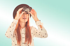 Composite image of smiling hipster woman using binoculars Stock Photography