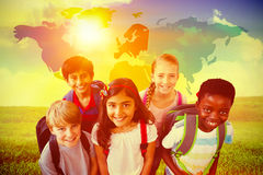 Composite image of smiling little school kids in school corridor Stock Image
