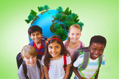 Composite image of smiling little school kids in school corridor Royalty Free Stock Photo