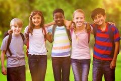 Composite image of smiling little school kids in school corridor Stock Photo