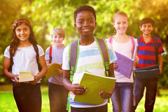 Composite image of smiling little school kids in school corridor Royalty Free Stock Images