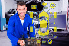 Composite image of smiling male machanic repairing car engine Stock Photo