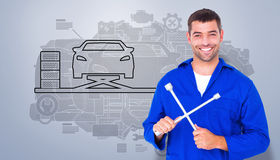 Composite image of smiling male mechanic holding lug wrench. Smiling male mechanic holding lug wrench against grey vignette Stock Images