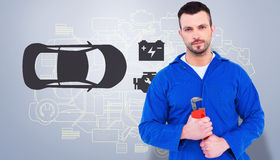Composite image of smiling male mechanic holding monkey wrench. Smiling male mechanic holding monkey wrench against grey vignette Stock Photo