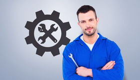 Composite image of smiling male mechanic holding spanner Royalty Free Stock Image