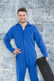 Composite image of smiling male mechanic holding tire Stock Image