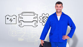 Composite image of smiling male mechanic holding tire Royalty Free Stock Photo