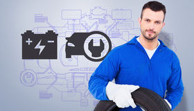 Composite image of smiling male mechanic holding tire Stock Photos