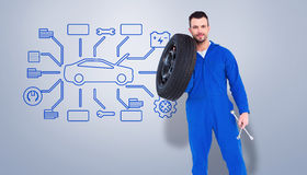 Composite image of smiling male mechanic holding tire Stock Images